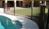 Smoothly curving pool fencing with ball tops on the posts